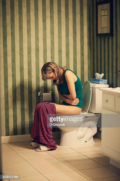 Woman in bathroom with stomachace