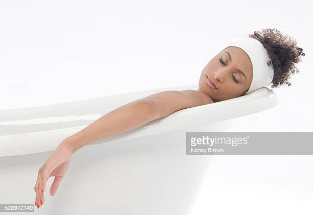 Woman in bathtub is sleeping.