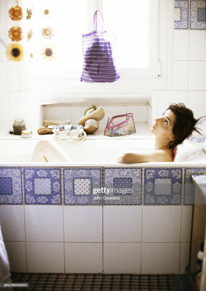 Woman in bathtub, looking up, side view : Stockfoto