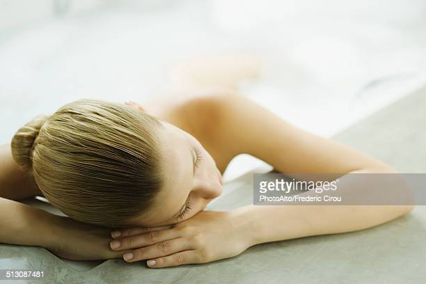 woman in bathtub resting head on side of tub - hydrotherapy stock photos and pictures