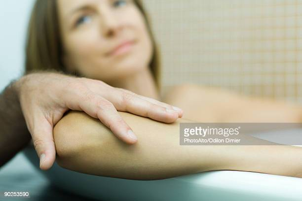 Woman in bathtub with man's hand on her elbow, , cropped view
