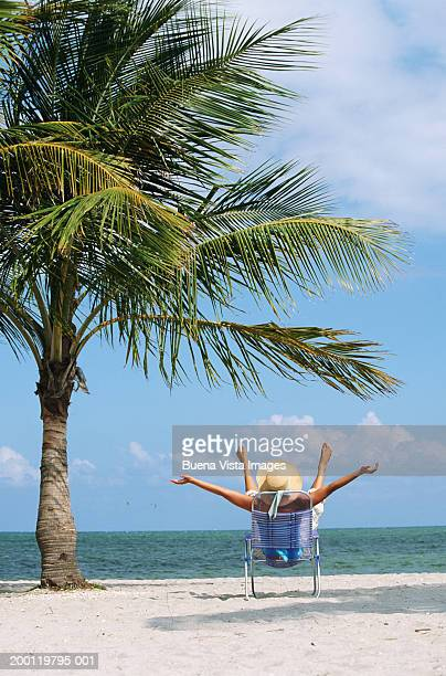 Woman in beach chair, ocean in background, rear view