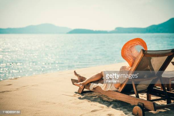 woman in beach chair - sun lounger stock pictures, royalty-free photos & images