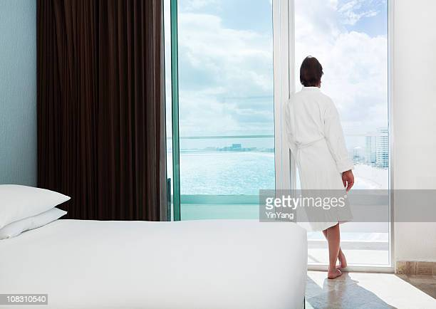 Woman in Beach Resort Hotel Room Relaxing, Admiring Balcony View