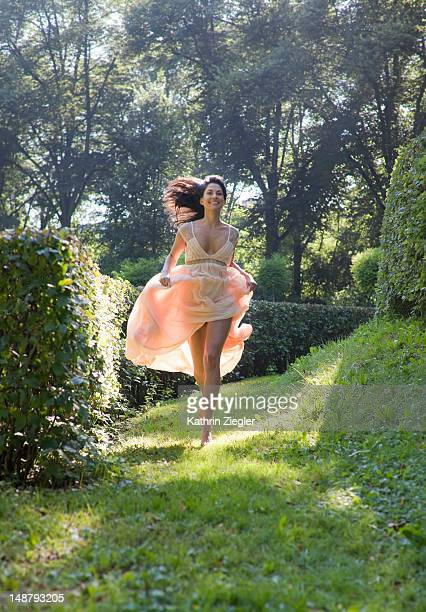 woman in beautiful dress running in the park - orange dress stock pictures, royalty-free photos & images