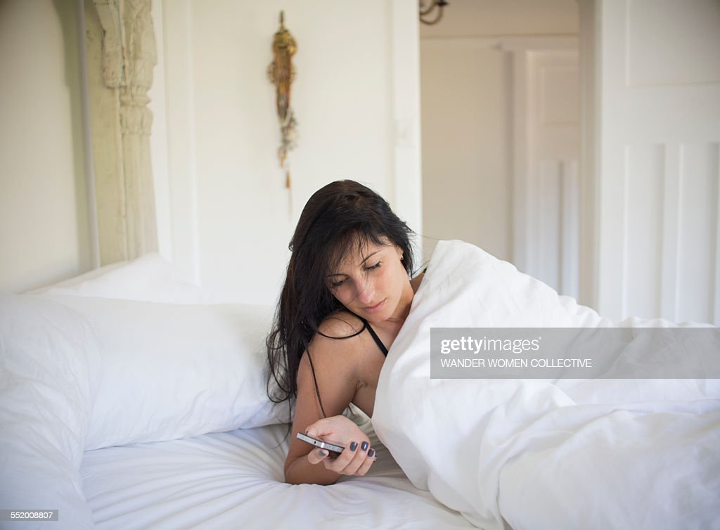 Woman in bed at home using smartphone ams texting : Stock Photo