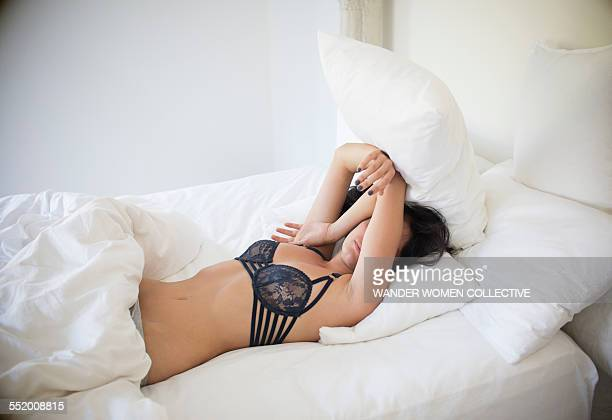 woman in bed at home waking up - dessous stock-fotos und bilder