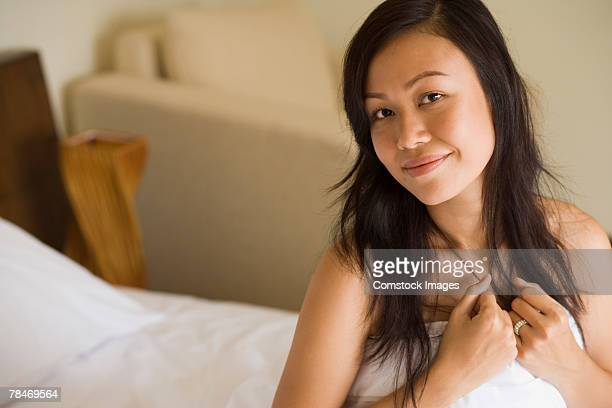 Woman in bed covering self with sheet