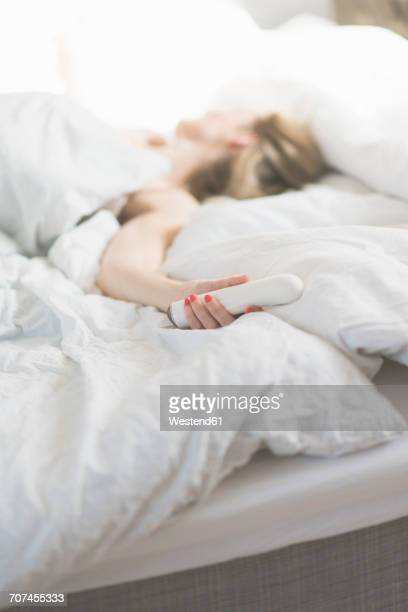 woman in bed holding sex toy - women touching herself in bed stock pictures, royalty-free photos & images
