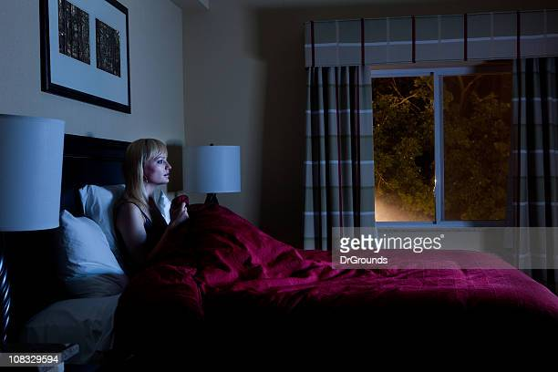Woman in bed late at night watching TV