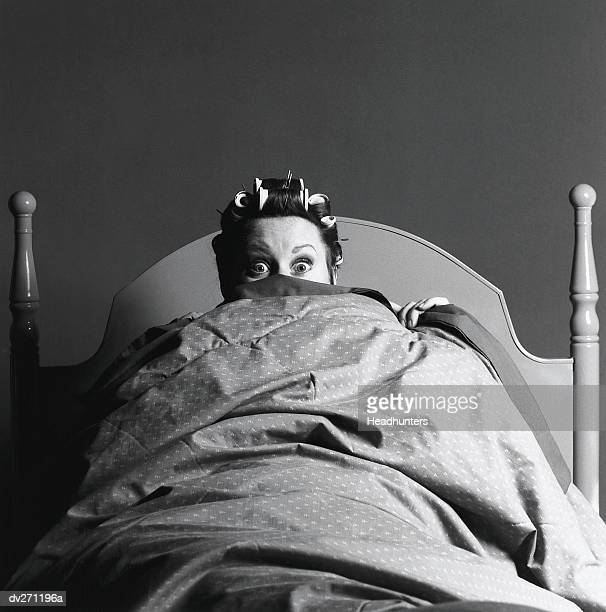 woman in bed peeking from blanket - headhunters stock pictures, royalty-free photos & images