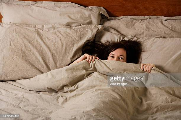 woman in bed peering out from under covers