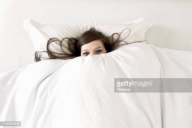 Woman in bed peering over top of duvet