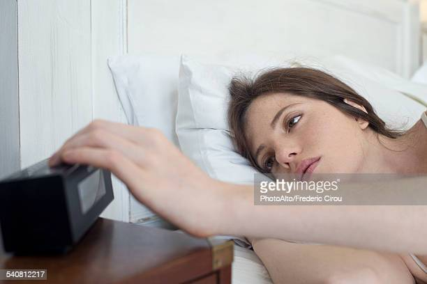Woman in bed pressing alarm clock snooze button