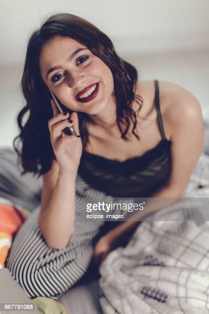 Woman in bed using a smart phone