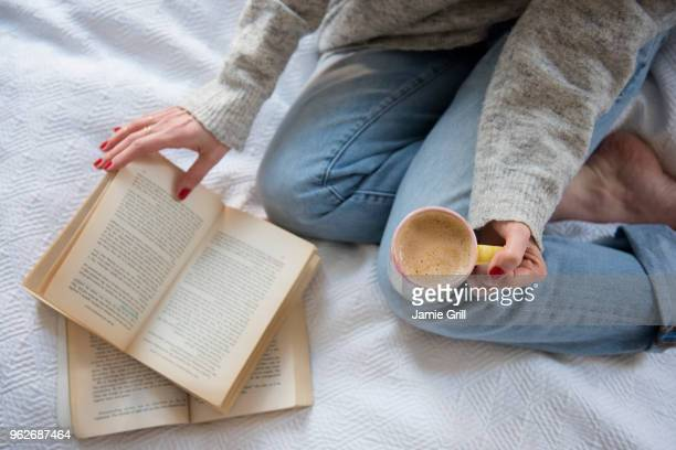 woman in bed with coffee and book - boek stockfoto's en -beelden