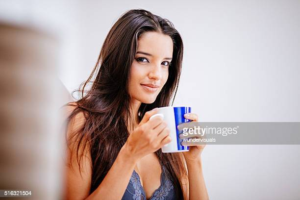 woman in bedroom is drinking a hot cup of coffee