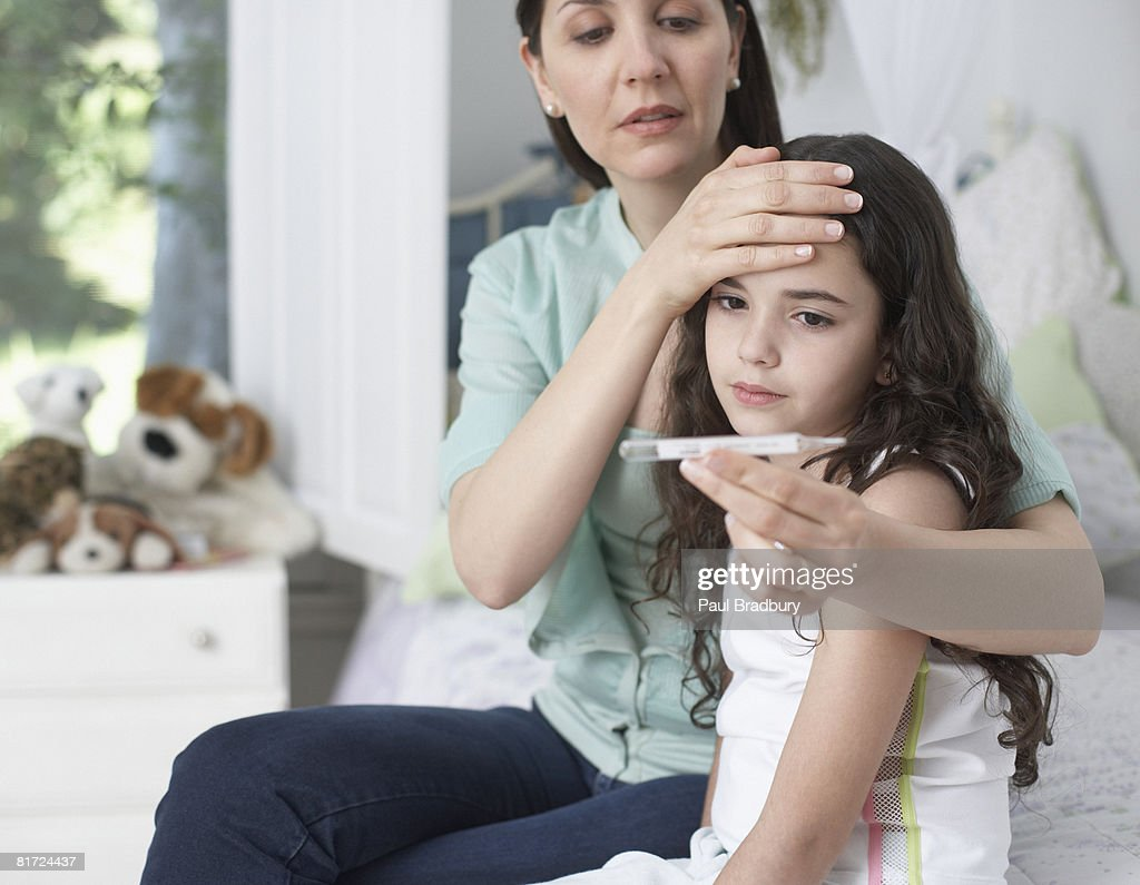 Woman in bedroom taking young girls temperature : Stock Photo