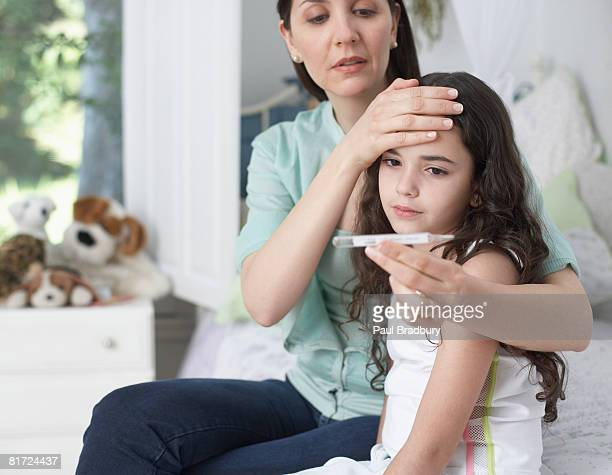 Woman in bedroom taking young girls temperature