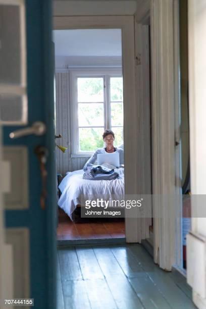 woman in bedroom using laptop - エーランド ストックフォトと画像
