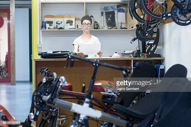 woman in bicycle workshop behind counter looking at paperwork - sigrid gombert stock pictures, royalty-free photos & images