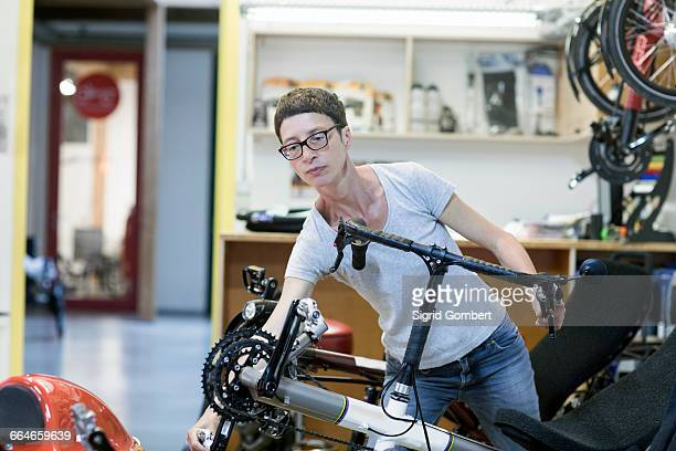 woman in bicycle workshop checking pedal on recumbent bicycle - sigrid gombert stock pictures, royalty-free photos & images