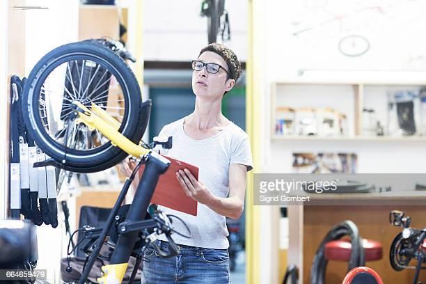 woman in bicycle workshop holding clipboard checking bicycle - sigrid gombert stockfoto's en -beelden