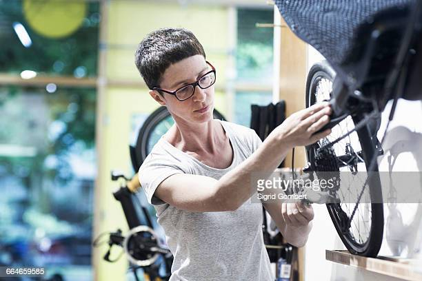 woman in bicycle workshop repairing wheel on recumbent bicycle - sigrid gombert stock pictures, royalty-free photos & images