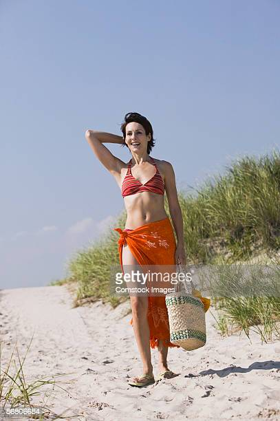 woman in bikini and sarong walking along beach - woman carrying tote bag stock photos and pictures