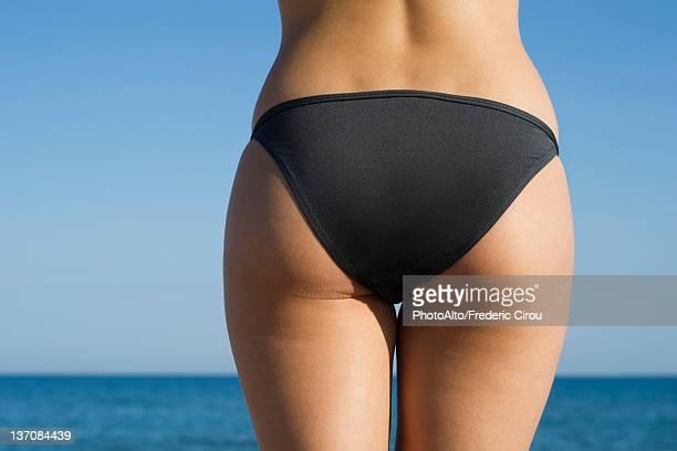 Woman in bikini at the beach, cropped rear view