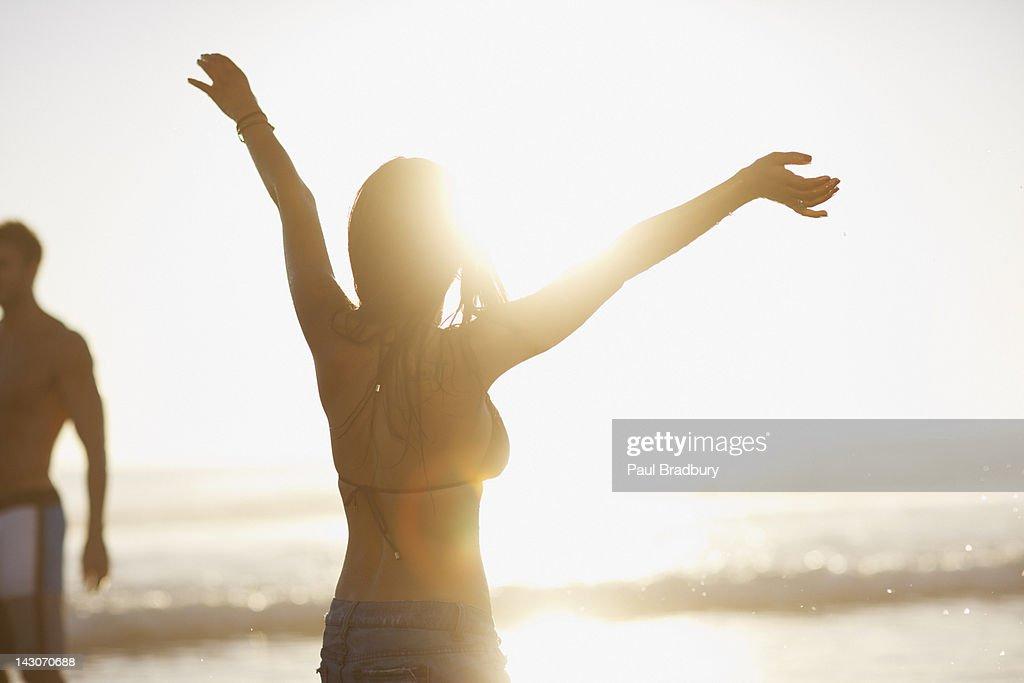 Woman in bikini cheering on beach : Stock Photo