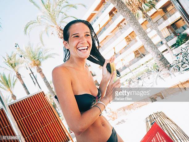 Woman in bikini combing her hair on the beach