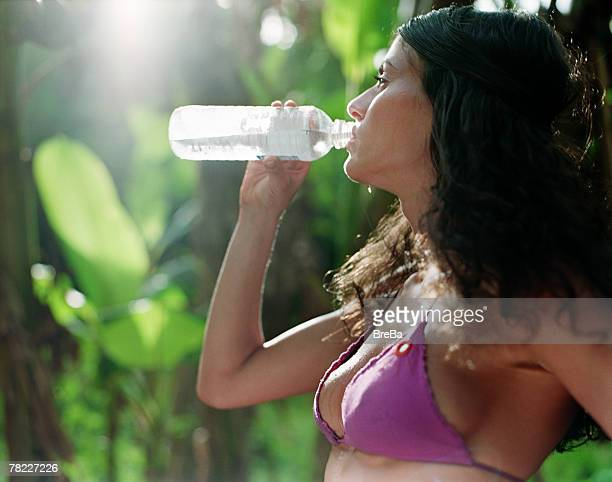 woman (25-30 years) in bikini drinking water from plastic bottle - 25 29 years stock pictures, royalty-free photos & images