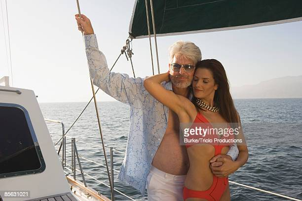woman in bikini embracing man on sailboat - sugar daddy stock photos and pictures