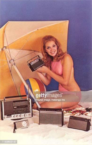 Woman in bikini holds a transistor radio and smiles