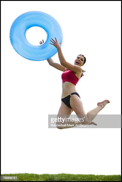 Woman in bikini jumping and smiling with swimming ring