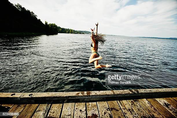 Woman in bikini jumping off of dock into lake