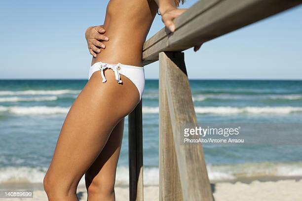 woman in bikini leaning against railing at the beach, cropped - mid section stock pictures, royalty-free photos & images