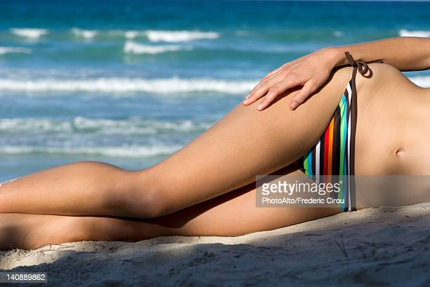 Woman in bikini lying on beach, low section