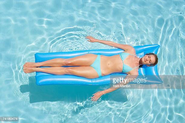 Woman in bikini on flotation device in pool