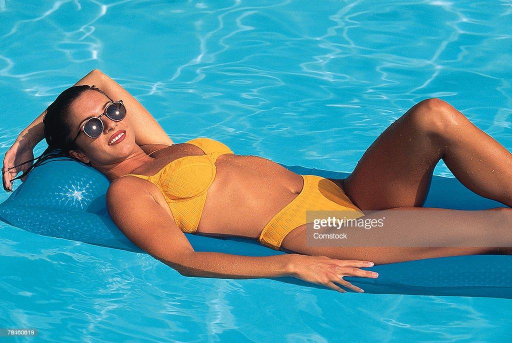 c03a26e7e Woman In Bikini On Raft In Swimming Pool Stock Photo - Getty Images