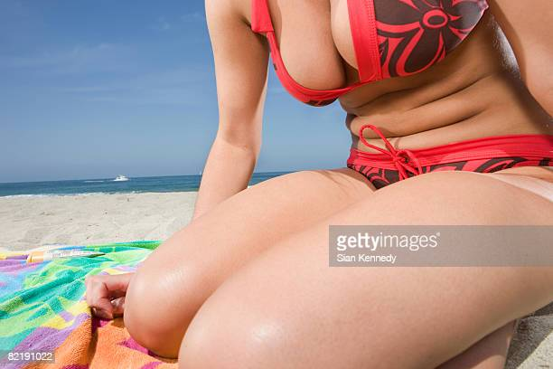 Woman in bikini on the beach, close-up of torso