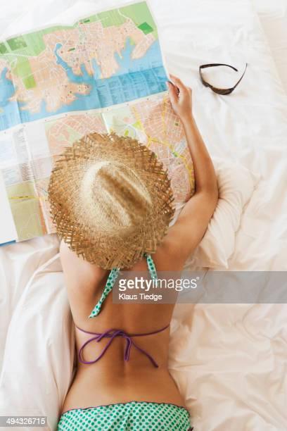 Woman in bikini reading map on bed