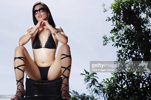 woman in bikini, resting head on hands, legs apart - legs apart stock photos and pictures