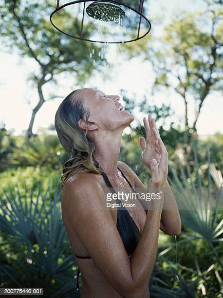 woman in bikini showering outdoors, side view - donna doccia foto e immagini stock