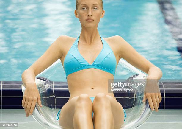 Woman in bikini sitting in transparent chair by pool