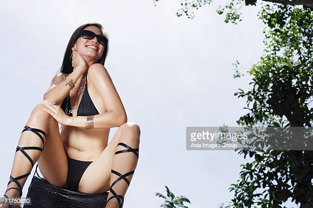 woman in bikini, sitting, legs apart, hand on neck - legs apart stock pictures, royalty-free photos & images