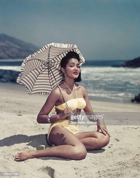 ビキニの女性に座るビーチパラソルを、笑顔、ポート