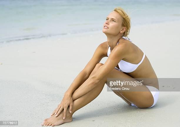 Woman in bikini sitting on beach, hugging knees, full length