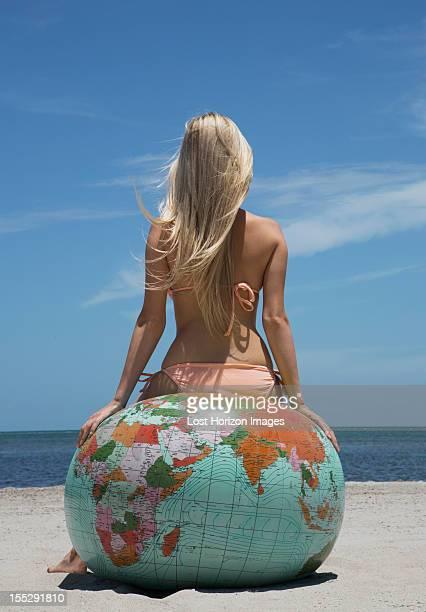 Woman in bikini sitting on globe